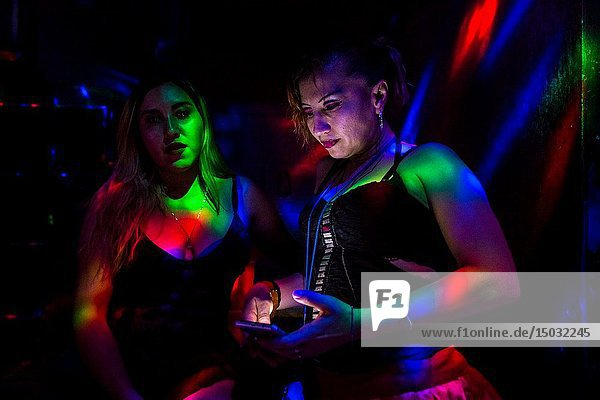 A Salvadoran sex worker looks at the phone screen while talking with her co-worker in a sex club in San Salvador  El Salvador  25 November 2018. Sex workersâ.task in the club is to be an entertaining and seductive companion. Performing erotic dance on the pole they make the customers stay as long as possible and buy relatively expensive alcoholic beverages from which they have a certain share. Sex workers are not obliged to have sexual intercourse with the club customers  they decide themselves  usually according to their current economic situation.