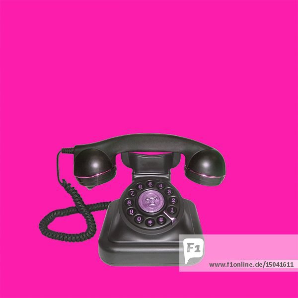Ringing Antique Telephone against Pink Background