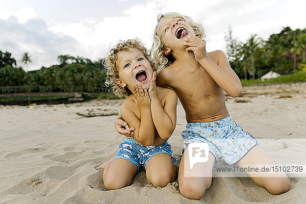 Brothers making faces on beach