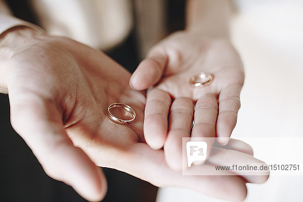 Hands of young couple holding wedding rings