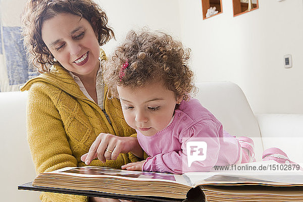 Mother and daughter reading picture book