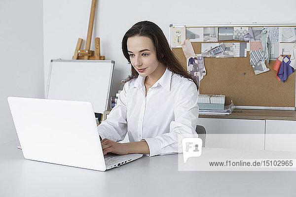 Fashion designer working at laptop
