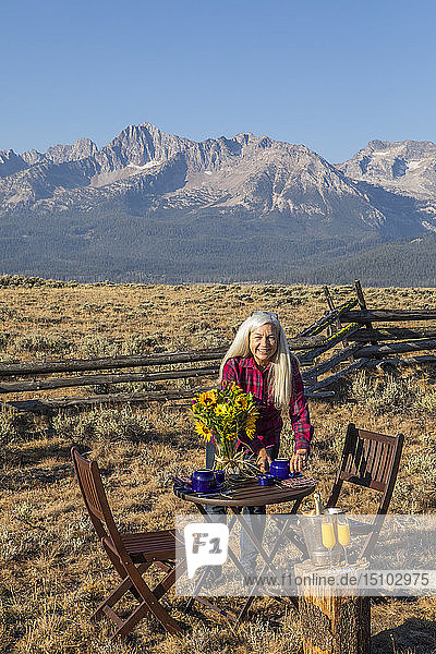Mature woman setting dining table in field by mountain in Stanley  Idaho