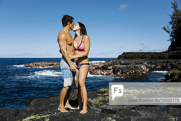 Couple kissing on rocks by sea