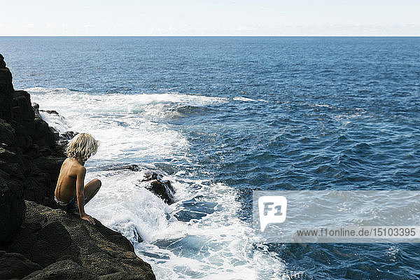Boy crouching on cliff by sea