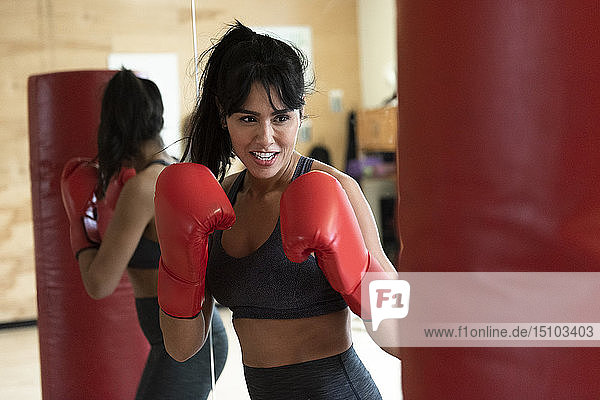 Woman boxing with punching bag