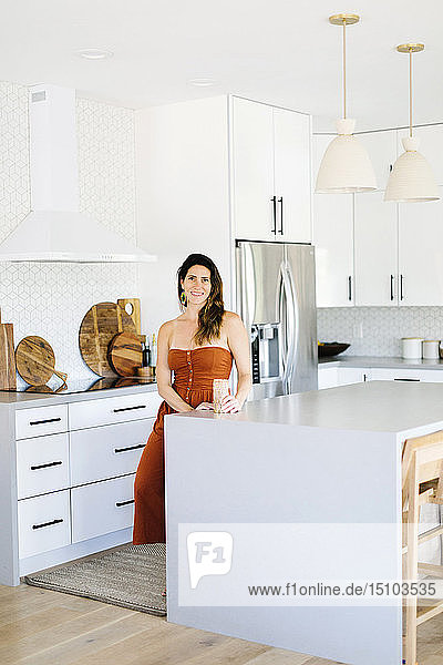 Mid adult woman smiling in kitchen