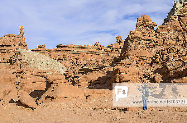 Woman photographing hoodoos in Goblin Valley State Park  Utah  USA