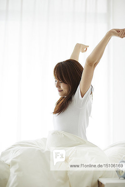 Young Japanese woman in bed in the morning