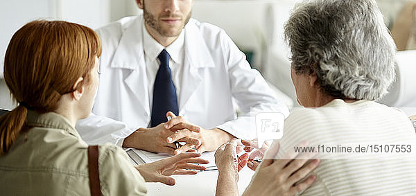Woman and her daughter talking with doctor