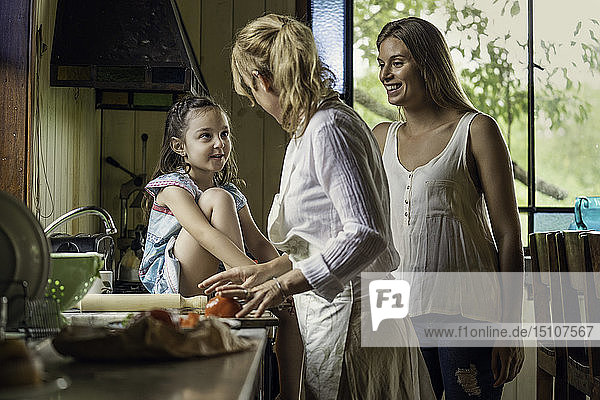 Mature woman talking with her granddaughter in kitchen