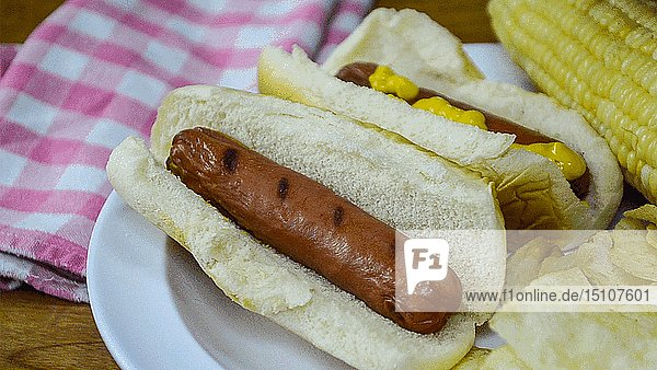 Hot Dog in Bun Opens its Eyes as another Hot Dog gets Squirted with Mustard