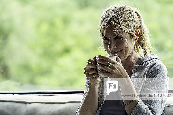 Mature woman having coffee at home