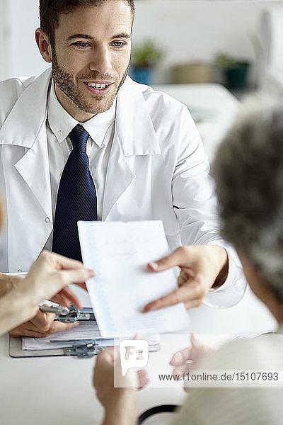 Doctor giving prescription to patient