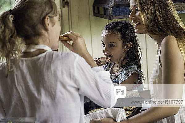Grandmother and granddaughter having cookies in kitchen