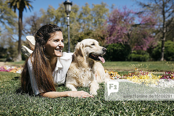 Happy woman lying on meadow in city park with her Labrador Retriever enjoying sunlight