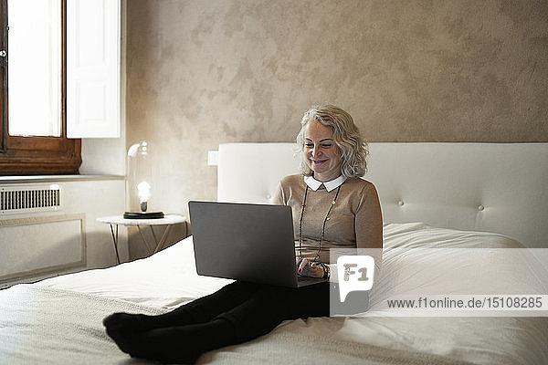 Porträt einer glücklichen reifen Geschäftsfrau  die am Bett sitzt und am Laptop arbeitet