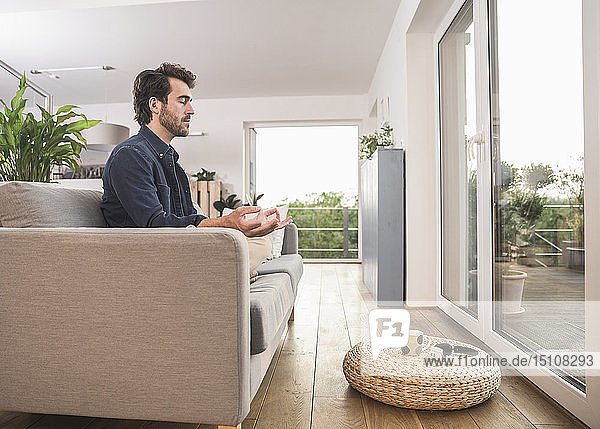 Junger Mann sitzt zu Hause auf dem Sofa und meditiert