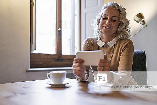 Porträt einer lächelnden reifen Geschäftsfrau  die mit einer Tasse Kaffee am Tisch sitzt und auf ihr Handy schaut