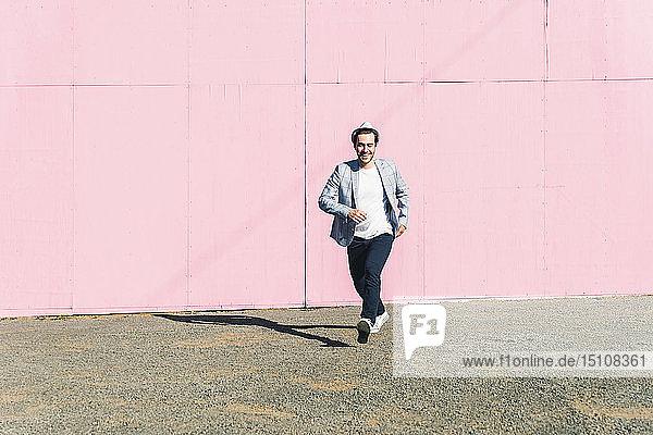 Junger Mann vor rosa Baustellenabsperrung  der sich in Bewegung setzt