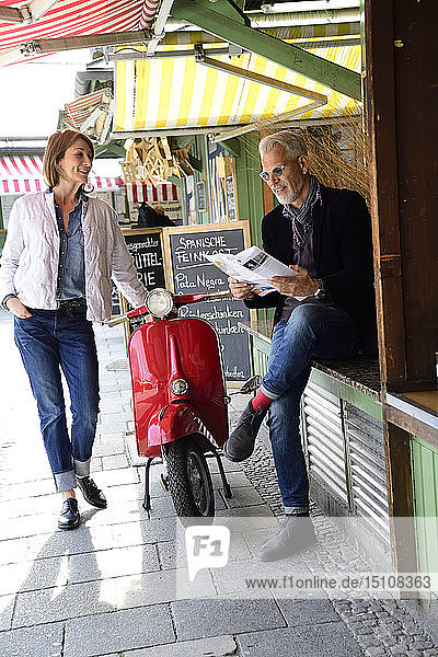 Mature couple meeting at the market  man raeding brochure