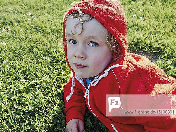 Porträt eines kleinen Jungen auf einer Wiese mit roter Jacke mit Kapuze