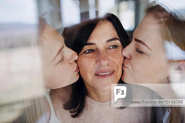 Besuchende Töchter  die ihre Mutter küssen und am Fenster stehen