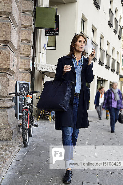 Mature woman smoking electronic cigarette in the city