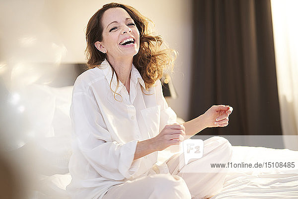 Laughing woman sitting on bed