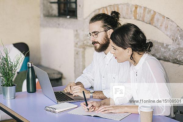 Junges Paar arbeitet bei Tisch zusammen