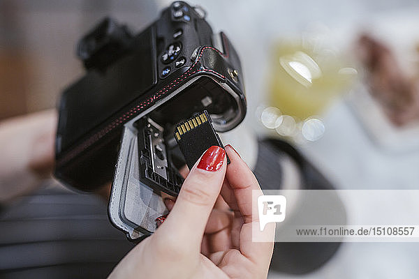 Close-up of woman putting chip into digital camera