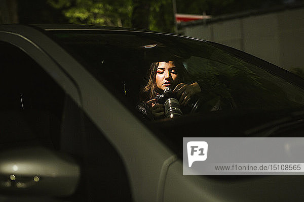 Young woman with camera in a car at night