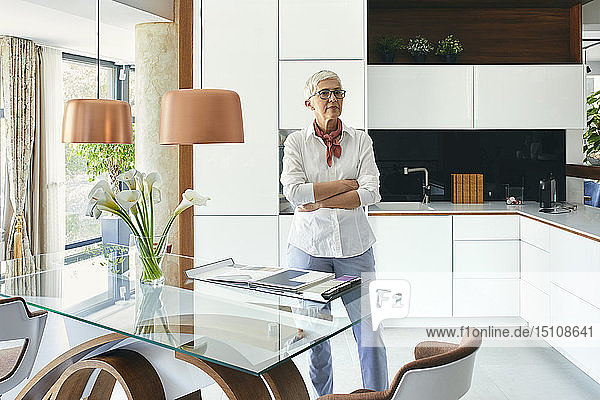Senior woman sitting on table in showroom of a furniture store  looking at catalogue