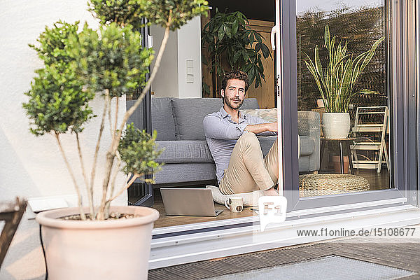 Young man relaxing in his comfortable home  looking out of window