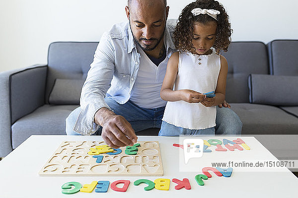 Father and daughter playing with alphabet learning game at home