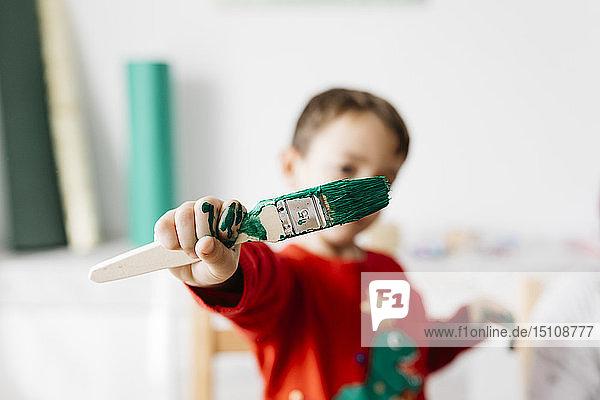 Kind mit einem Pinsel in der Hand beim Basteln zu Hause