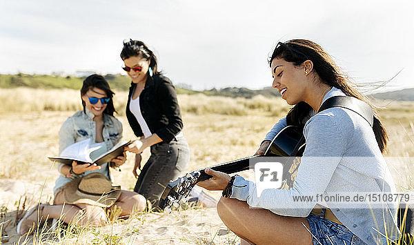 Junge Frau mit Freunden spielt Gitarre am Strand