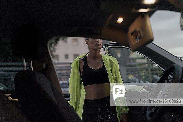 Sportliche Frau steigt nach dem Training ins Auto ein