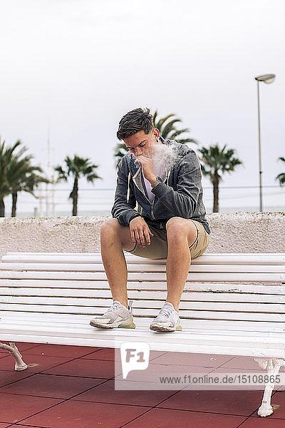 Junger Mann raucht einen Joint mit Palmen im Hintergrund