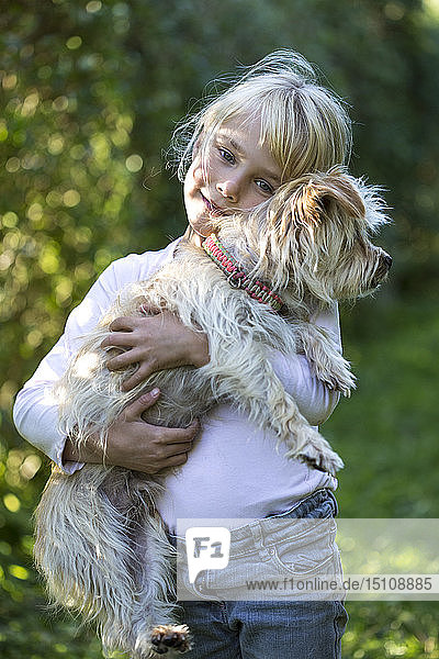 Portrait of happy little girl with her dog in the garden