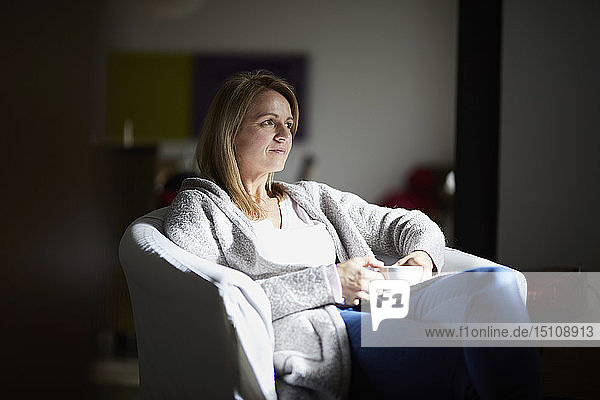 Woman sitting at home  relaxing in arm chair