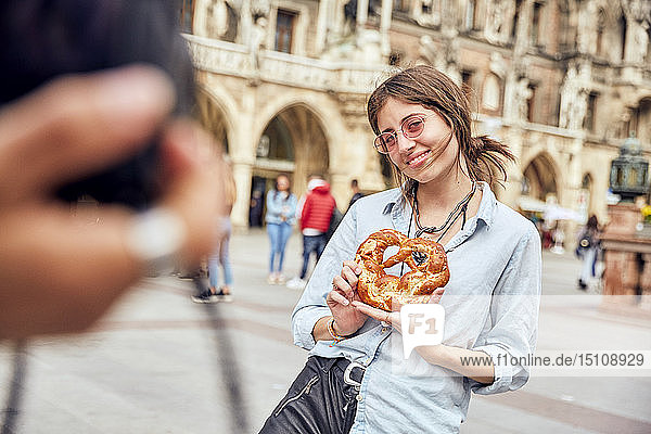 Young couple taking a photo  woman with brezel in Munich  Germany