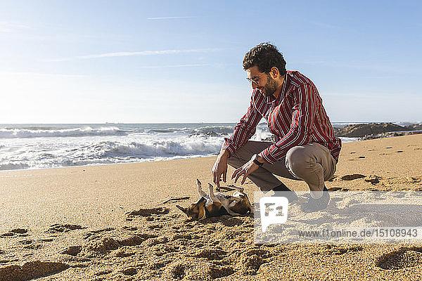 Portugal  Porto  junger Mann spielt mit seinem Hund am Strand