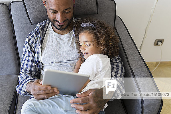Father and daughter sitting on couch at home together looking at tablet