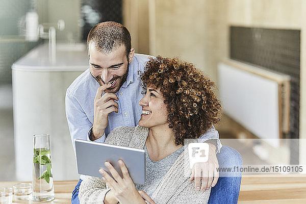 Glücklicher Mann und Frau teilen sich ein Tablett in einem modernen Büro