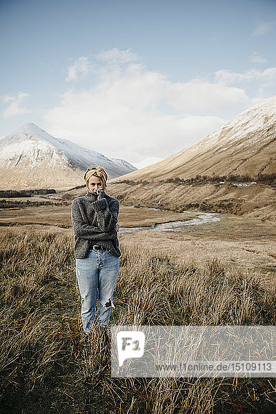 UK  Scotland  Loch Lomond and the Trossachs National Park  young woman standing in rural landscape