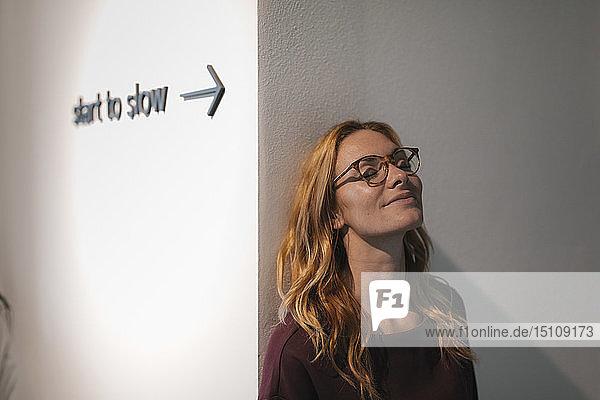 Junge Frau lehnt mit geschlossenen Augen an einer Wand