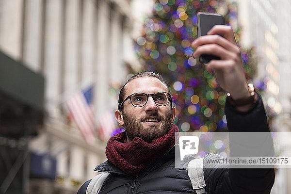 Porträt eines Touristen  der sich mit einem Smartphone vor einem beleuchteten Weihnachtsbaum selbstständig macht  New York City  USA