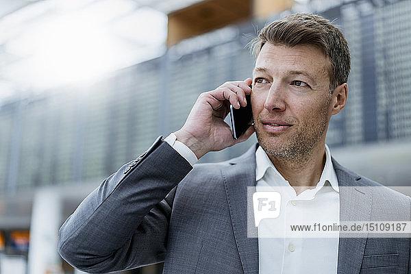 Porträt eines Geschäftsmannes auf dem Handy am Flughafen