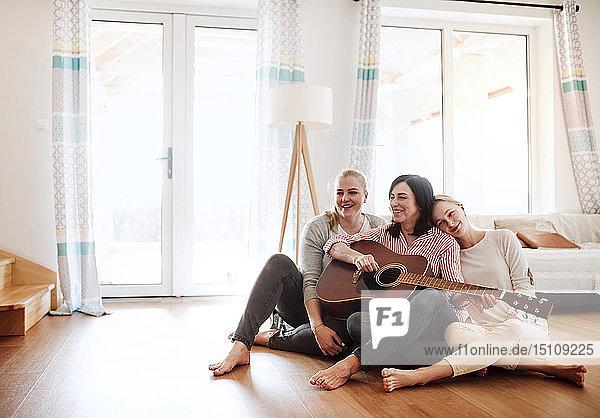 Reife Frau mit zwei Töchtern  die zu Hause auf dem Boden sitzen und Gitarre spielen